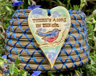 """Beautiful pine needle basket with """"There's A Song In The Air"""" heart pottery bird pendant and dyed blue magnesite base entitled """"Bird Song""""."""