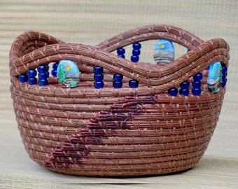"""Enchanting reddish brown pine needle basket with gorgeous colorful scenic lampwork beads and a maple wood base entitled """"Nature's Majesty""""."""