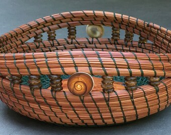 """Gorgeous brown and dark green pine needle basket with Operculum shell beads, African beads and a wood burl base entitled """"Northwest Shores""""."""