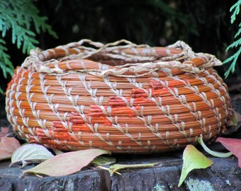 "Lovely orange and brown pine needle basket with orange horse chestnut leaf pottery base entitled ""Autumn""."
