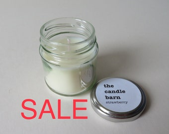 Strawberry scented candle in a small silver screw top glass jar,