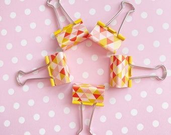 Yellow geometric binder clips with triangles in pink, coral and mustard