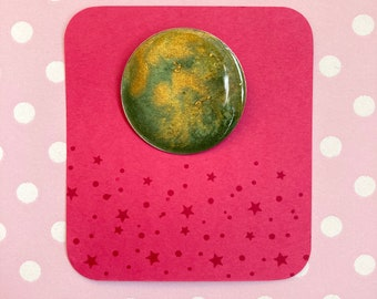 Green brooch with a shimmery gold cloud effect. Unusual round brooch made with resin.