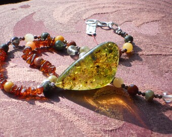 Amber mysteries are in this dramatic green amber pendent and the golden amber bead chain framed by faceted quartz beads.