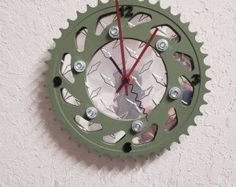 Sprocket clock. Used sprocket painted olive drab, with aluminum diamond tread on the back, black numbers and red hands.