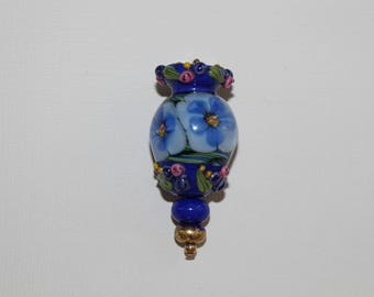 Stunning lampwork pendant in hues of blue with tiny pink roses and blue flowers under the glass