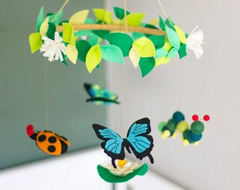 Bug baby mobile featuring butterflies, ladybird, caterpillar and lily pad with flower in lush greens and blue.