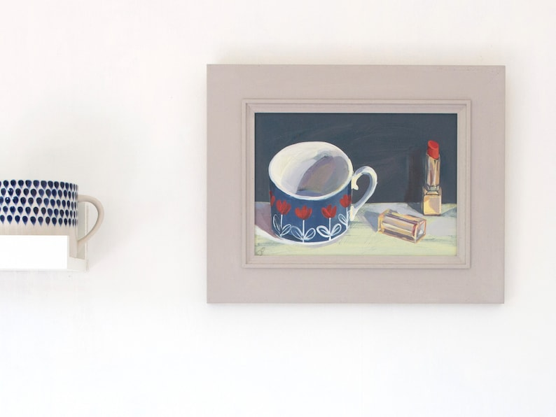 A vibrant red lipstick and cup still life painting  framed in image 0