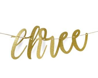 """Gold """"Three"""" Glitter Script Banner, Third Birthday Party, Anniversary, Number Banner, Photo Prop, Word Banner, Custom Banner, Sparkle, 3"""
