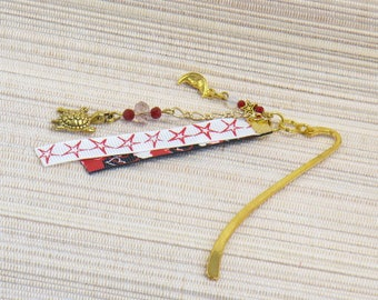 Bookmark in metal gilded with his turtle and moon, and red and white ribbons