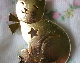"""Vintage ULTRACRAFT happy smiling cat.  Brushed gold metal with cut out star and dangling heart.  Signed """"Ultracraft""""."""