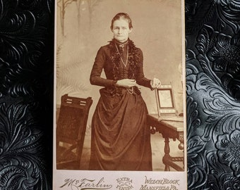 Victorian cabinet card photo woman in mourning with her hand on a framed photo wearing beautiful jewelry Mansfield Pennsylvania McFarlin