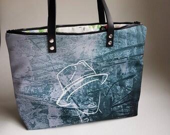Heavy canvas shoulder bag in hand or worn