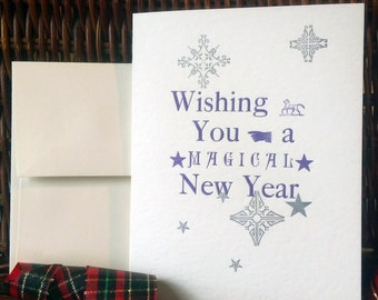 wishing you a magical new year card letterpress printed with metal types and ornaments with off white envelope