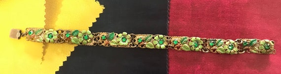 Dainty Victorian gold metal bracelet with green enamel flowers and emerld green stones