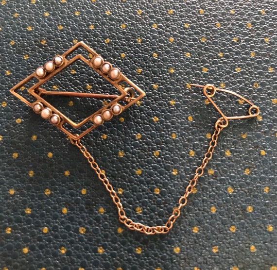 Edwardian diamond shaped brooch with peaarls and a safety chain