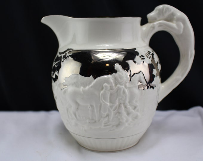 Mid-century (1950s) Wedgwood Barlaston Etruria Devonshire pitcher. Embossed hunting scenes, figural dog handle.