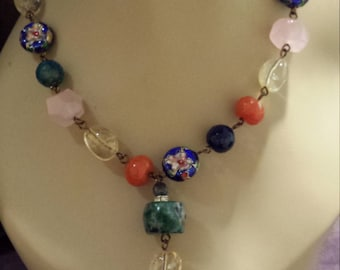 One strand necklace made with faceted assorted stones and colors and center drop