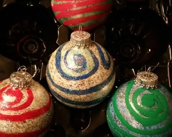 White glass ornaments with painted spirals & glitter.