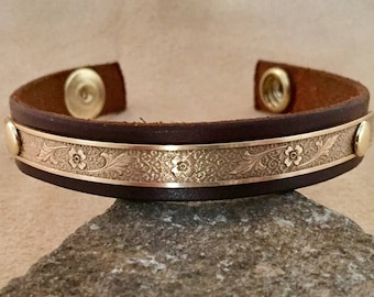 Leather cuff with floral brass accent.
