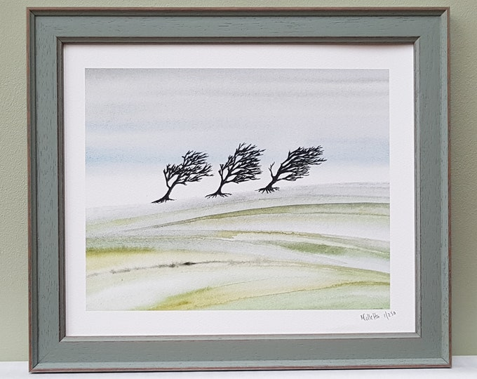 A framed winter scene print of trees on pastel green hills from a watercolour, pen and ink painting. Signed limited edition artwork.