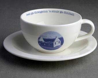 Deserted by a Woman and Defied by the Rudder - Ceramic tea cup & saucer with decal print titled 'bean ga thrèigsinn is stiùir ga dhiùltadh