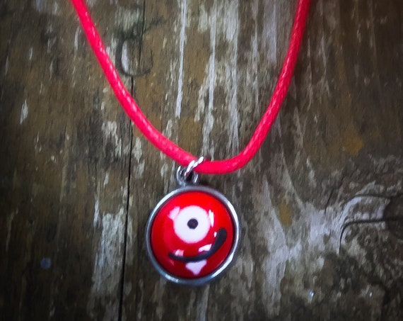 Halloween necklace, little monster in glass and Tin on a necklace cord.