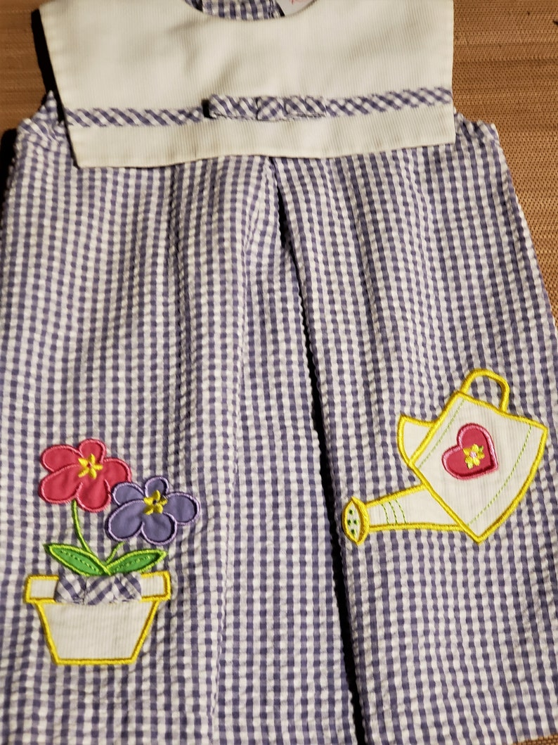 with decrotive watering pot An adorable little girl grape  blue vintage gingham dress Free Shipping and a flower pot of daisy flowers.