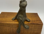 Vintage Brass Frog Statue that sits on a flat surface edge