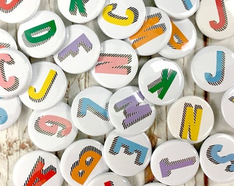 Alphabet pin badges. Word lover. Letter Button rainbow of colours. ''Bradford Buzz' font. Small 25mm, Large 38mm Name initial A-Z