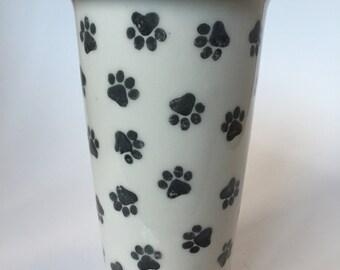Ceramic travel mug decorated with black paw prints