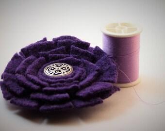 Purple felt flower with decorative metal button center