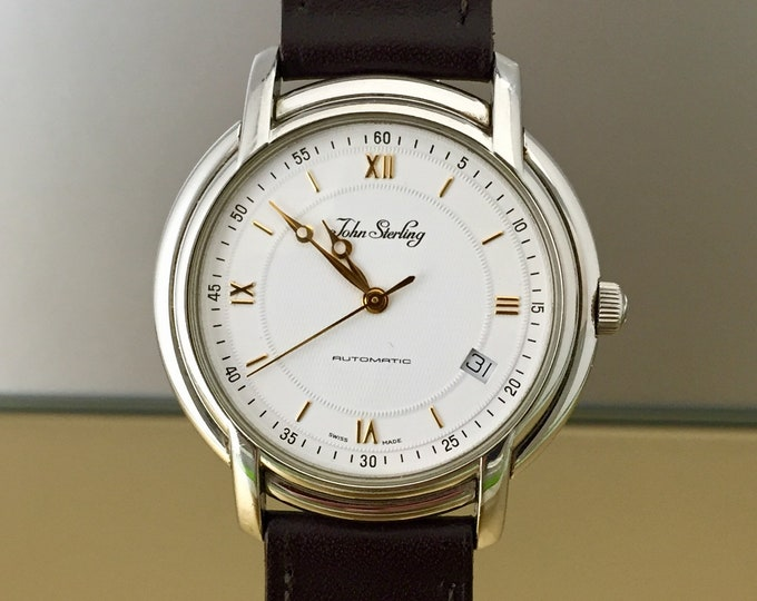 Elegant 90-year clock automatic JOHN sterling with visible movement.