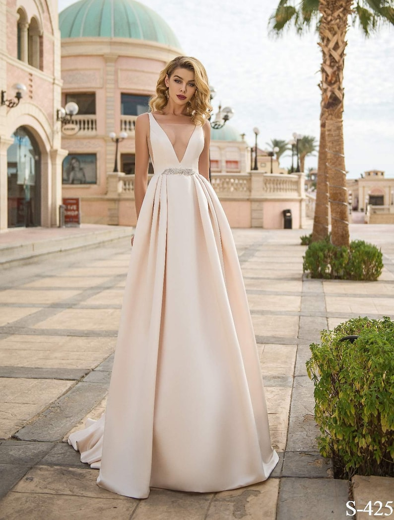 1c2b0a7bdb40 Light pink satin wedding dress with a plunging neckline in