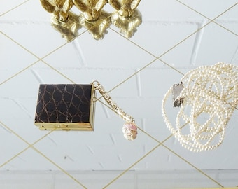 rectangular pill box in gold-coloured metal with embossed brown faux leather and a pendant, vintage pill squeezing