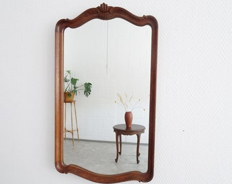 large mirror in antique style with carved floral details, oak mirror