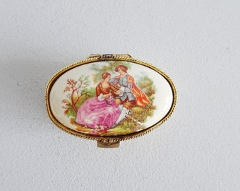 oval pill box in gold embossed metal with baroque pair in Fragonard style, vintage pill squeaks, jewelry storage