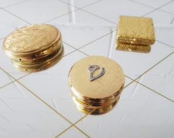 gold-colored pill boxes in various shapes, vintage metal pill boxes