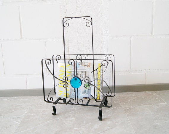 black newspaper stand made of wrought iron and ocean blue glass stone
