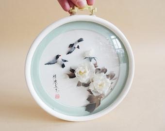 runder Bilderrahmen mit asiatischem Vogelmotiv und Blüten aus Federn