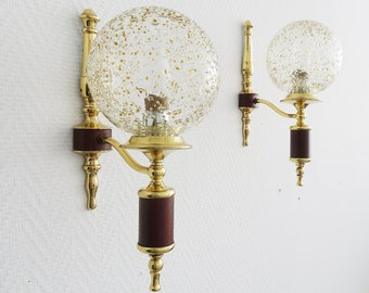 golden wall lamps with round glass shades and teak veneer