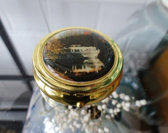 round pill box divided into gold-colored with ship motif, vintage pill boxes
