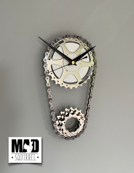 Sprocket and Chain Clock, representing the main sprocket and rear cassette of a bicycle. With a white face and black hands