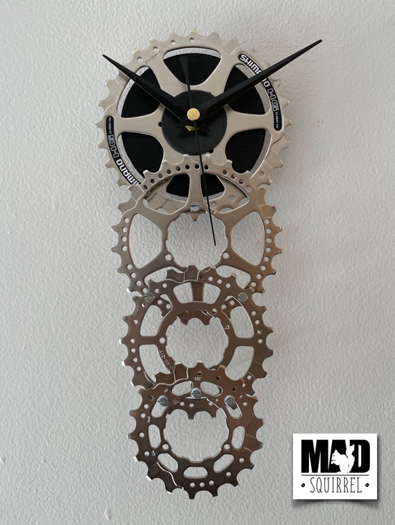 Four Sprocket Step Clock with black face and hands and a carbon fibre support leg.
