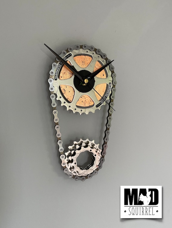Sprocket and Chain Clock, representing the main sprocket and rear cassette of a bicycle. With a weathered copper leafed face and black hands