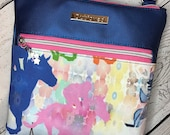Crossbody bag with equestrian theme racehorses. Electric blue textured vinyl, silver hardware.