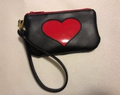 Black faux leather wristlet with rounded corners, red patent heart reverse applique detail, pink waterproof canvas lining. Size small.