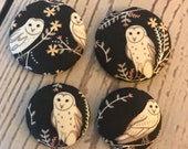 SET OF FOUR Fabric covered button magnets - snowy owl with flowers on black magnets two 1 1/8 inch diameter and two 1 7/8 inch diameter