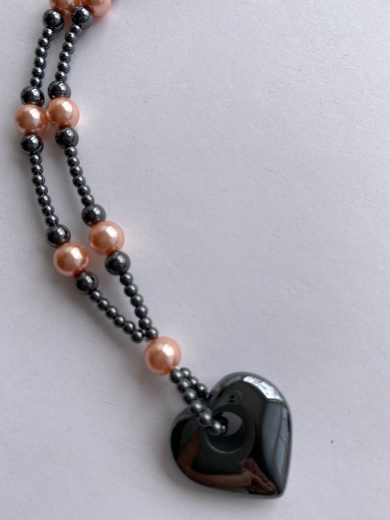 Pretty princess length necklace of shiny gray hematite round beads and pale pink glass pearls with a hematite heart pendant.