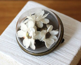 Glass brooch with true white flowers